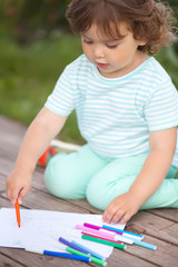 Cute toddler girl drawing with felt-tip pens