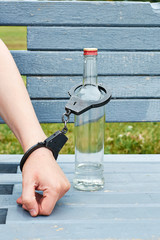 Man in handcuffs interconnected with a bottle of vodka