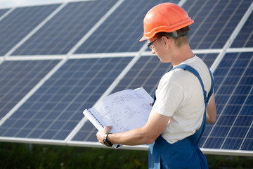 Young worker in overall looking in drawings at solar power station. Employee in blue overall and orange helmet, looking in technical documentation.