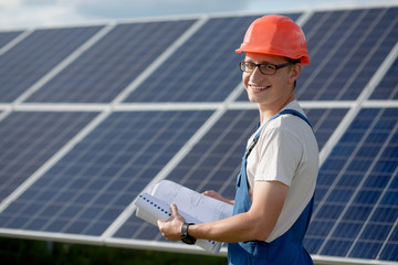 Young man working with solar panels. Worker at solar power station holding documents looking in camera and smiling.