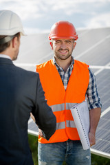 Foreman shaking hand to a business client. Worker in orange helmet and vest with a client in business suit an white helmet, solar panels at backstage.