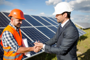 Businessman holding photovoltaic detail and shaking hand to a foreman. Solar panels in the field, business deal between client and foreman.