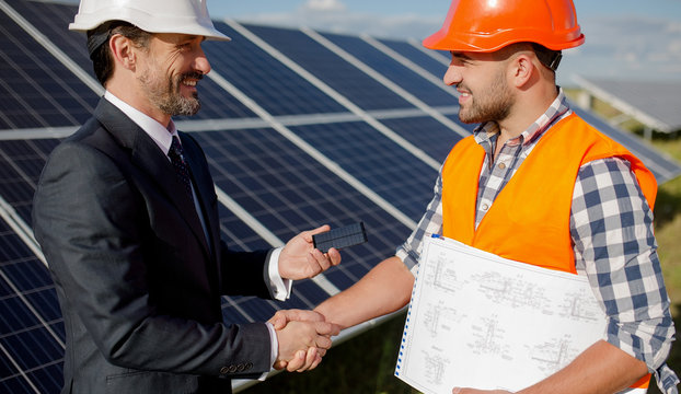 At solar energy station business client and foreman shaking hands. Two men making deal, shaking hands, solar panels on backstage.