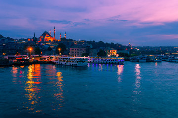 Landscape view of night city near of Galata Bridge, Istanbul, Turkey. Panoramic seaview on Golden Horn Bay in blue hour. Famous tourist and islam east destination