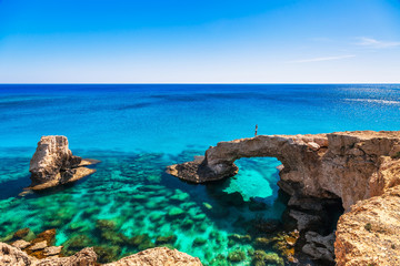 Printed kitchen splashbacks Cyprus Woman on the beautiful natural rock arch near of Ayia Napa, Cavo Greco and Protaras on Cyprus island, Mediterranean Sea. Legendary bridge lovers. Amazing blue green sea and sunny day.