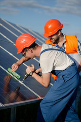 Technicians installing photovoltaic panels at solar power station. Workers checking solar panels equipment.