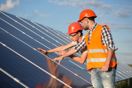 Worker and foreman maintaining solar energy panel. Technicians checking equipment for solar energy station.