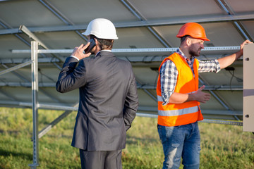 Director and engineer, solar panels construction. Head of solar station talking on phone.