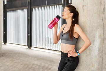 Relaxed young woman enjoying refreshing beverage after running
