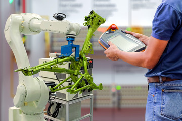 Engineers use a wireless remote control of robotic workpiece for smart factory, industry 4.0 concept