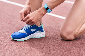 Legs of female runner adjusting shoelaces on running shoe
