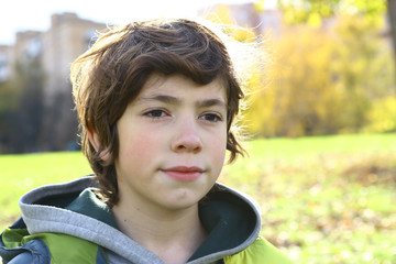 teen boy close up portrait in autumn city park