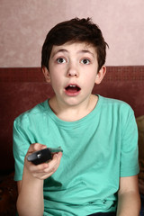 teenager boy watch movie with remote control close up photo