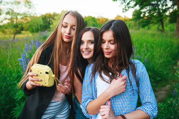 Three hipsters girls blonde and brunette taking self portrait on polaroid camera and smiling outdoor. Girls having fun together in park.