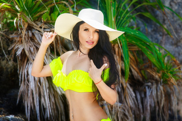 Beautiful brunette with long hair in bikini and straw hat on the jungle on a tropical beach. Summer vacation concept.
