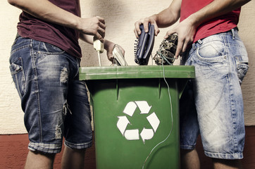 E waste concept, two man putting electronic waste into recycle bin