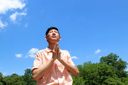 Young asian man praying and meditating in a outdoor park with blue sky and clouds