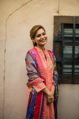 Pakistani woman in traditional clothing standing next to her house, posing and smiling