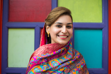 Smiling young Pakistani lady in front of a colorful door