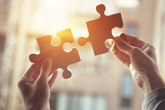 Businesswoman hand connecting jigsaw puzzle with sunlight effect, Business solutions, success and strategy concept.