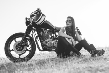 Black-and-white portrait of a beautiful biker woman sitting by her motorcycle Wall mural
