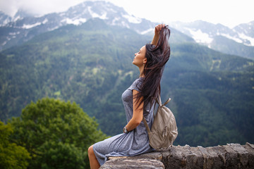 Beautiful tourist girl with backpack at mountains