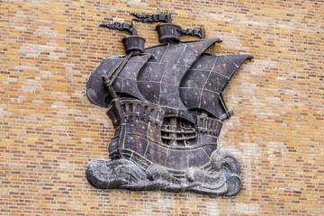 Relief eines historischen Segelschiffes an einer Hauswand