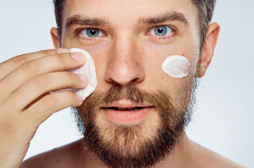 Young guy with beard on white isolated background apply cream