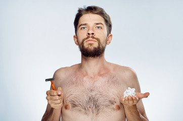 Young guy with a beard on a white isolated background holds a razor and shaving gel
