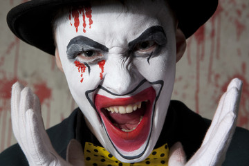 Evil clown wearing a bowler hat on wall