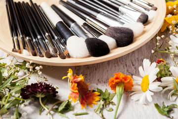 Professional Make up brushes on plate next to wild flowers on wooden background