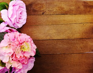 space wooden background with artificial flowers bouquet