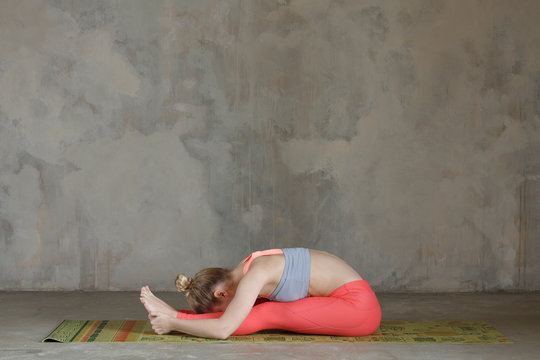 Young woman practicing left seated forward bend / Paschimottanasana yoga pose against texturized wall / urban background