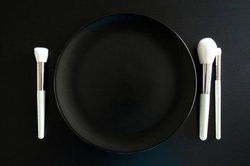 Conceptual image of make up brushes next to dinner plate on black background