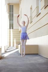 Ballet dancer dancing on street. Young ballerina on yellow background full length