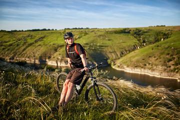 Mountain bike adventur. Cyclist has a rest on riverside.