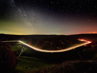 Night sky with milky way and stars, night road illuminated by car's light trails