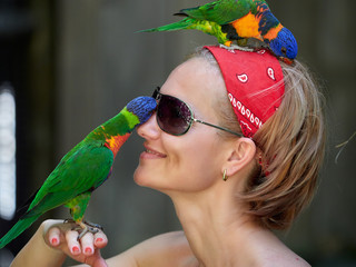 young woman with funny colorful parrot on her head