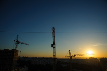 tower cranes silhouette at construction site