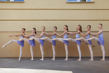 Ballet dancers dancing on street. Young ballerinas on yellow background full length