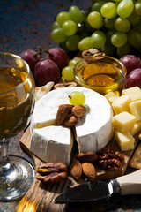 snacks, wine and Camembert cheese on a dark background, vertical, closeup