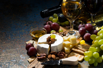 snacks, wine and Camembert cheese on a dark background