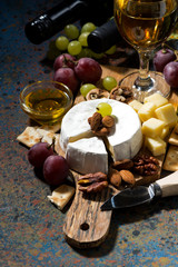snacks, wine and Camembert cheese on a dark background, vertical, top view