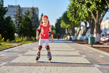 Girl riding on roller skates in skatepark summer outdoor. Child in a red suit for the rollers