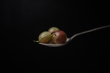 Gooseberry isolated over black background.
