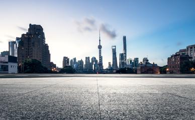 empty brick platform with Shanghai skyline in background.
