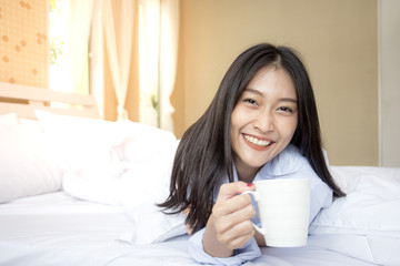 Happy young asian woman hold coffee cup with attractive smiling, 20-25 years old.