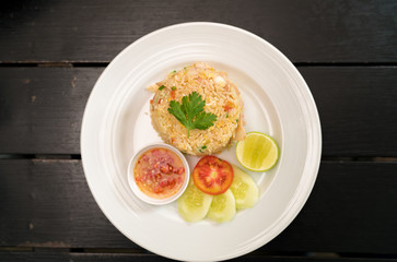 Thai Healthy food : fried rice chicken with egg and green coriander leaves and side dish.  (Asian fried rice) view from above on dark wood.
