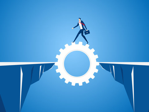 Businessman using cog gear to cross through the gap between hill.  Business risk and success concept.