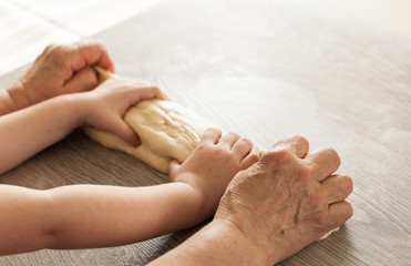 Women's hands and children's hands knead the dough, the banner for the bakery. Close-up with place for text
